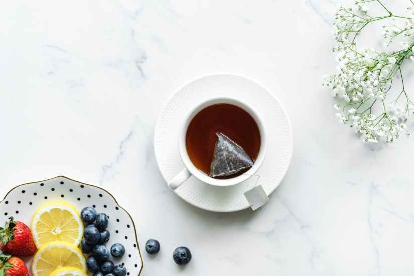 flat lay photography of tea in white teacup with saucer